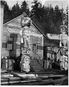 Totem poles in front of homes at Alert Bay Photographer/Studio: Timms, Philip Downing, C.S. Topic: Totem poles Indian wood-carving Thunderbird (Legendary character) Location: British Columbia - Alert Bay
