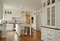 white kitchen with timber floors and glass pendants