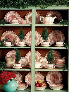 A matching set of mid-20th-century Currier & Ives transferware really shines in this green cupboard. Mini trees in teacups complete the look.