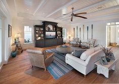 Old Florida Home by Weber Design Group - coastal decor with a white sofa, brown arm chair and black wall entertainment center