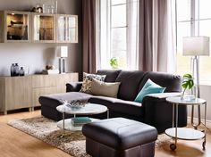 Salón con sofá de cuero de dos plazas marrón oscuro con chaise longue y reposapiés. Combinado con una mesa de centro redonda y almacenaje efecto nogal.