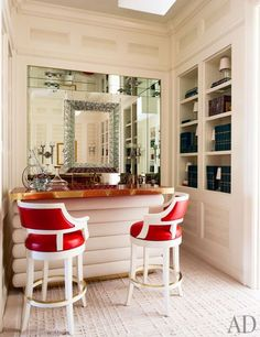 A Roberto Giulio Rida mirror reflects the bar area, which gets cheerful pops of color from Gregorius|Pineo stools covered in an Edelman leat...