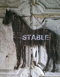 """Constructed of plank wood with a dark, vintage finish Sign is shaped in the likeness of a horse White text across center of sign reads """"STABLE"""" in uppercase, di"""