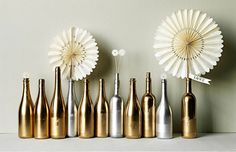 On each table for a centrepiece -  use a few bottles, jars and vases sprayed gold with white flowers and black and white windmills randomly placed??