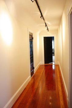 Love the idea of track lighting in a hallway + black doors