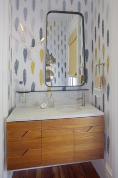 Cool Powder Room: feather wallpaper, soothing palette of gray and yellow. Sink and mirror being offset just makes sense. Antler Sconce -fun.