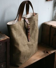 What an amazingly cool bag. Olive green, waxed canvas, with aged leather straps and patina'd brass buckles. -KWA