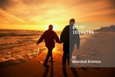 sunsets with the elderly | Stock Photo : Elderly couple walking on beach, sunset, rear view