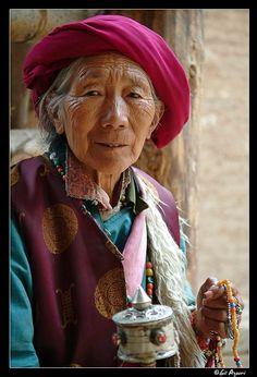 Tibet, village de Yubeng, comté de Deqin - Femme âgée tibétaine  tenant dans sa main gauche un mala tibétain et dans sa main droite, un moulin à prières - Photographe : Gil Azouri / Prise de la photo : 16 Juin 2005 / www.gilazouri.com