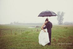 rainy day wedding photos in a field. black umbrellas.  Fraser River Lodge wedding by White Album Weddings