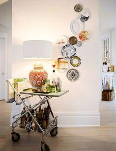 bar cart, lamp, plate wall
