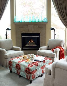 """Cozy Seating Area  """"Aqua and red are a powerful combination. Hickory Chair's Inman ottoman is covered in Eliana from William Yeoward. Oly blue resin vases."""""""