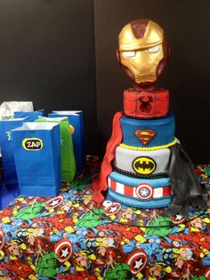 Superhero montage cake from today! Fondant covered. Spider-Man, Super man, Batman, and Captain America. Four tiers of white buttermilk with Swiss Buttercream. Iron man decorative keepsake topper. For Hayden's 7th birthday.