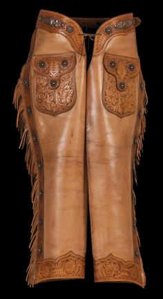 "Classic shotgun chaps in the California style. Deep floral tooling with silver accents. Fringe the full length of the legs, zippers added to the sides. Nice light color. Identified in the 1934 Visalia Catalog as ""Walker Chaps - Oh Boy"" No. 1929."