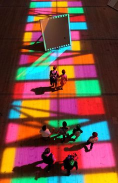 """People look at a light show by French artist Daniel Buren entitled """"Catch"""" which is on display until Oct. 12, 2014 at the BALTIC Centre for Contemporary Art in Gateshead, northeastern England, Wednesday, Aug. 6, 2014."""