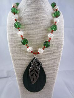 Necklace with forest green glass beads, acrylic rhinestones, seed beads & teardrop pendants.