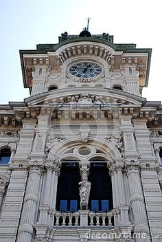 Photo made at the town hall tower in Piazza Unità d'Italy in Trieste in Friuli Venezia Giulia (Italy). In the picture you see the top of the tower with the large mullioned window of the balcony framed by two columns, with the clock by Roman numerals in circles.