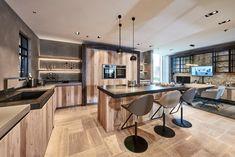 Deze keuken met kookeiland heeft ruimte voor drie barkrukken. De L-vormige keuken langs de muren biedt nog veel meer extra werkruimte. Deze eiken keuken heeft een aanrechtblad van beton én van graniet. Hoe gaaf is dat?