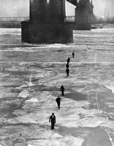 People walk across the frozen Mississippi River from East St. Louis to St. Louis on Feb. 12, 1936. The Municipal (later MacArthur) Bridge piers are in the background. (Lou Phillips, St. Louis Post-Dispatch)