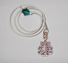 "Beautiful ""Snowflake Bay"" bookmark with a green swarovski crystal attached to one end and a ""Whimsical Christmas Tree"" charm attached at the other end to keep your place as you read ""Snowflake Bay""."