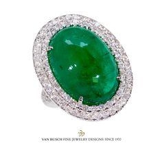 21 ct., center mounted cabochon emerald, surrounded by 2.10 ct. round, brilliant-cut diamonds. Shown in 18k white gold.