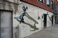 hese black and white figures are so realistic, pedestrians might be mystified when they pass by this wall mural by Norwegian stencil artist Anders Gjennestad. Also known as Strøk, the artist utilizes all kinds of visual tricks, including distorted perspective and strong shadows, to produce illusions of people walking sideways on walls.