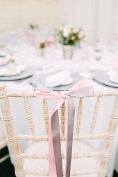 Pink & Grey Ribbons tied in a bow on the backs of the chairs - Image by Hayley Savage Photography - Pronovias 'Leonela' Wedding Gown & Coast Bridesmaid Dresses with No.1 by Jenny Packham Accessories in a Marquee at Hill Place with Pink & Grey Colour Scheme & Church Flower Arch.