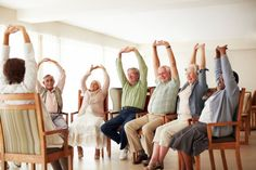 Daily stretching exercise routine for a group of cheerful elderly people at an old age home.