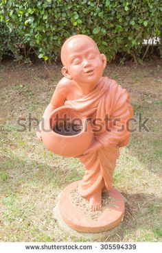 Buddhist novice holding alms bowl clay doll at Thai Buddhist temple - stock photo