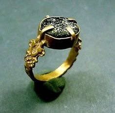 Byzantine, 400-600 AD. Gold and glass stone ring. Dark blue glass stone set in gold band with designs on the sides.