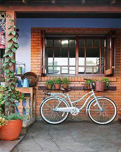 Os novos ares foram conquistados com uma cobertura de madeira que forma uma varandinha na frente da casa, muitas flores, um banho de azul na parede e adornos recolhidos em antiquários e viagens ao longo da vida do morador e da família.