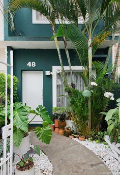 Área externa de casa pintada de verde, piso de cimento queimado e muitas plantas.