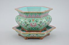"Chinese Export Porcelain Hexagonal Famille Rose Flower Pot and Under Plate, ca. 19th Century. A hand enameled footed pot with footed under plate. Painstakingly painted with flowers on a pale green background, pink rims and turquoise insides. Unsigned and unmarked. Pot measures . 4""H x 6-5/8""W and plate 1-1/2""H x 7-3/4""W."