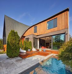 A modern home with a curved roof has a small front courtyard with a swimming pool and sun deck. Custom Home Builders, Custom Homes, Quebec, Roof Design, House Design, Cottage Design, Vancouver, Parametric Architecture, Front Courtyard