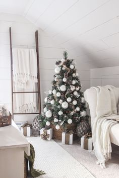 Simple monochromatic Christmas tree.  Simple natural accents with white everything else.