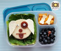 Here is a cute little doggie easylunchbox. Again, I placed romaine lettuce down in the larger compartment and placed my dog sandwich on top. The dog sandwich was cut into a circle with my comfort grip circle cutter. I used white tortilla for the ears, fruit leather for the eye patch, nose, and mouth and icing eyes. The other compartments held crackers with dogbone shaped cheese and some blueberries with a doggie pick.