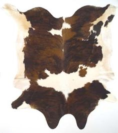 tricolor exotic cowhide rug tossed on a stained cement floor flooring