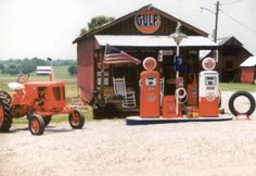 Gulf sign, gas pumps and antique tractor <3
