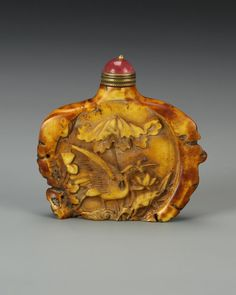 China, carved horn snuff bottle, in organic form, with carved bird and floral motifs, a red stopper, and the natural striations of the horn visible. Height 2 1/2 in.