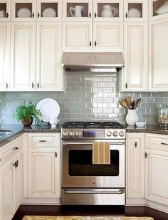 antique white glazed cabinets blue subway tile more traditional/rustic style kitchen