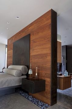 Stone with pebbles is a unique mix in this bedroom. The contrast creates a strong focal point at the bed with the timber feature wall and textured stones.