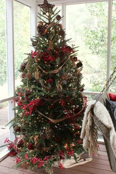 """""""The porch Christmas tree was trimmed again with pinecones, grapevine wreath garland, red berry garland, and balls of red berries and more grapevine.  I added some of the jute webbing that I used in the kitchen, but it seemed too large in scale, so I cut it in half to use on the tree."""""""