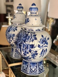 A pair of blue and white Delft lidded vases, Chinoiserie inspired with a pair of birds and floral peony images. The porcelain jars are octagonal in shape and have a ribbed exterior, with lids surmounted by acorns. There are original Delft markings to the bottom showing the pharmacy bottle with the intertwined initials of JT (Joost Thooft, the owner of the company in 1876).  Dimensions:  H500 x W280mm  Code: 24EA274