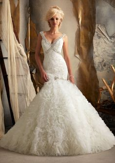 Exquisitely fashioned with crystal beading, Alencon lace and perfectly ruffled tulle, this Mori Lee 1902 wedding gown will please you with its mermaid styling and superb beading that criss crosses over the bodice to make shoulder straps that grace the bodice. Then the straps give way to create a keyhole effect over the back and fabulous covered buttons stretch over the derriere. #timelesstreasure