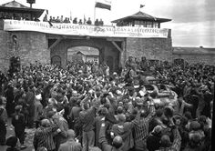"""Liberated prisoners in the Mauthausen concentration (Austria), give rousing welcome to Cavalrymen of the 11th Armored Division. The banner across the wall was made by Spanish Loyalist prisoners. It says """"LOS ESPAÑOLES ANTIFASCISTAS SALUDAN A LAS FUERZAS LIBERADO-RAS"""" (""""The Spanish Antifascists greet the Liberating Forces""""). The text is written in English and Russian (""""Испанские антифашисты приветствуют освободителей"""") as well."""