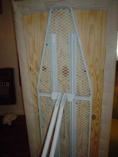 Use an old ironing board and some plywood to create quilting rack