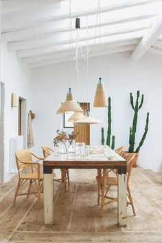 Nanimarquina Residence - An existing skylight draws sunshine into the dining area, where PET lamps by Álvaro Catalán de Ocón dangle over vintage wicker chairs (from a local maker) and a salvaged-wood table by Piet Hein Eek. Photography by Albert Font. Dining Room Design, Dining Area, Dining Table, Dining Rooms, Custom Cushions, Wicker Chairs, Furniture Movers, Affordable Furniture, Wide Plank