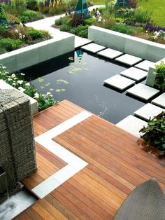 Geometric designs create a bold landscape in this contemporary backyard, featuring a shallow pond with a unique square walkway made of stone. A chic wooden deck anchors the outdoor space.