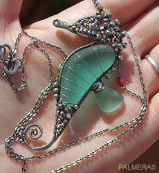 """As an artist Rasuleva is inspired by """"the beauty, colors, and nature of the Mediterranean Sea."""" One day during her walk, she found several curved shards of teal sea glass.  """"I held them in my hands, and suddenly I had an idea to create a seahorse,"""" says Rasuleva, who explains """"I adore the seahorse. I consider it to be a unique and mythical sea creature.""""  """"I did not even imagine it could work out until I finished it,"""" she says.  Rasuleva now sells her sea glass pendants and other creations…"""