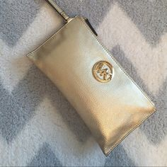 Michael Kors Gold wristlet /clutch Michael Kors Gold Clutch , perfect for going out and special occasions . Used once for a weeding  in perfect conditions  Michael Kors Bags Clutches & Wristlets